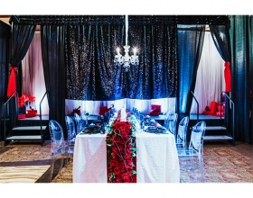 seated dinner with red and black decorations and a chandelier
